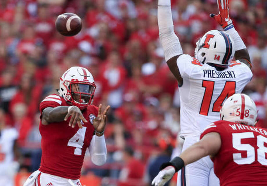 FILE - In this Oct. 1, 2016, file photo, Nebraska quarterback Tommy Armstrong Jr. (4) throws under pressure from Illinois defensive lineman Gimel President (14) during an NCAA college football game in Lincoln, Neb. Nebraska faces Indiana this week. Armstrong and Indiana quarterback Richard Lagow could put on quite an air show Saturday. They're ranked second and third in the Big Ten in passing efficiency with nearly identical numbers. (AP Photo/Nati Harnik, File)