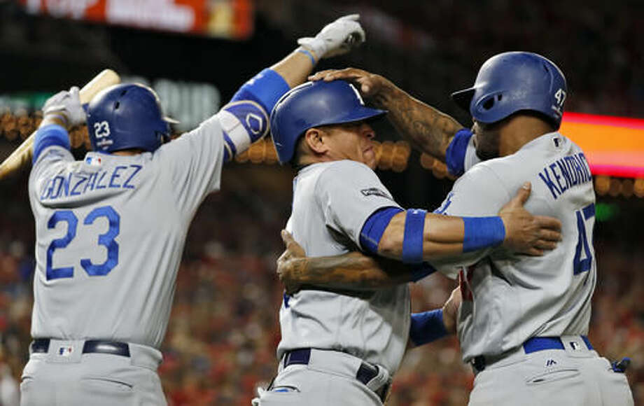 Los Angeles Dodgers' Adrian Gonzalez, left, Carlos Ruiz and Howie Kendrick, right, celebrate after Ruiz and Kendrick scored on a triple by Justin Turner during the seventh inning in Game 5 of a baseball National League Division Series against the Washington Nationals, at Nationals Park, Thursday, Oct. 13, 2016, in Washington. The Dodgers won 4-3 to advance to the NLCS. (AP Photo/Alex Brandon)