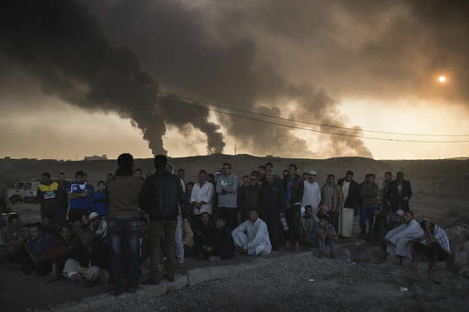 Men are held by Iraqi national security agents, to be interrogated at a checkpoint, as oil fields burn in Qayara, south of Mosul, Iraq, Saturday, Nov. 5, 2016. Islamic State fighters launch counterattacks in the thin strip of territory Iraqi special forces have recaptured in eastern Mosul, highlighting the challenges ahead as the battle moves into more densely populated neighborhoods where coalition air power must be used more selectively. (AP Photo/Felipe Dana)