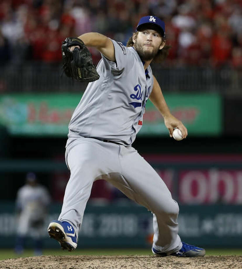 Los Angeles Dodgers pitcher Clayton Kershaw winds up during the ninth inning of Game 5 of a baseball National League Division Series, against the Washington Nationals at Nationals Park early Friday, Oct. 14, 2016, in Washington. The Dodgers won 4-3. (AP Photo/Alex Brandon)