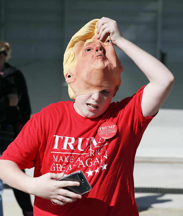Nate Horne pulls off his Donald Trump mask as he arrives for a rally for Republican presidential candidate Donald Trump Saturday, Nov. 5, 2016, in Wilmington, N.C. (AP Photo/John Bazemore)