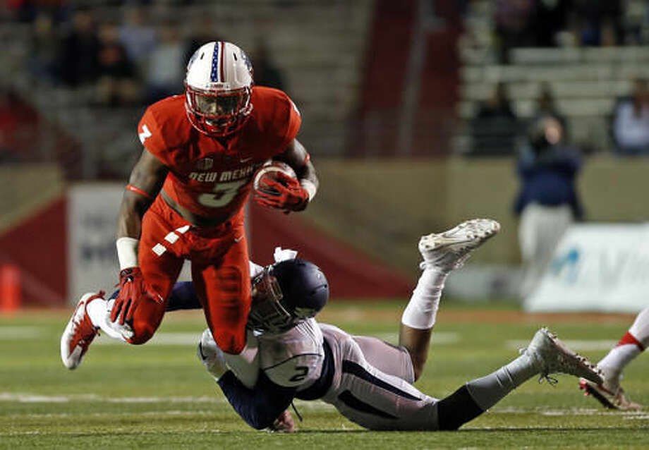 New Mexico running back Richard McQuarley (3) is tackled by Nevada defensive back Asauni Rufus during the first half of an NCAA college football game in Albuquerque, N.M., Saturday, Nov. 5, 2016. (AP Photo/Andres Leighton)