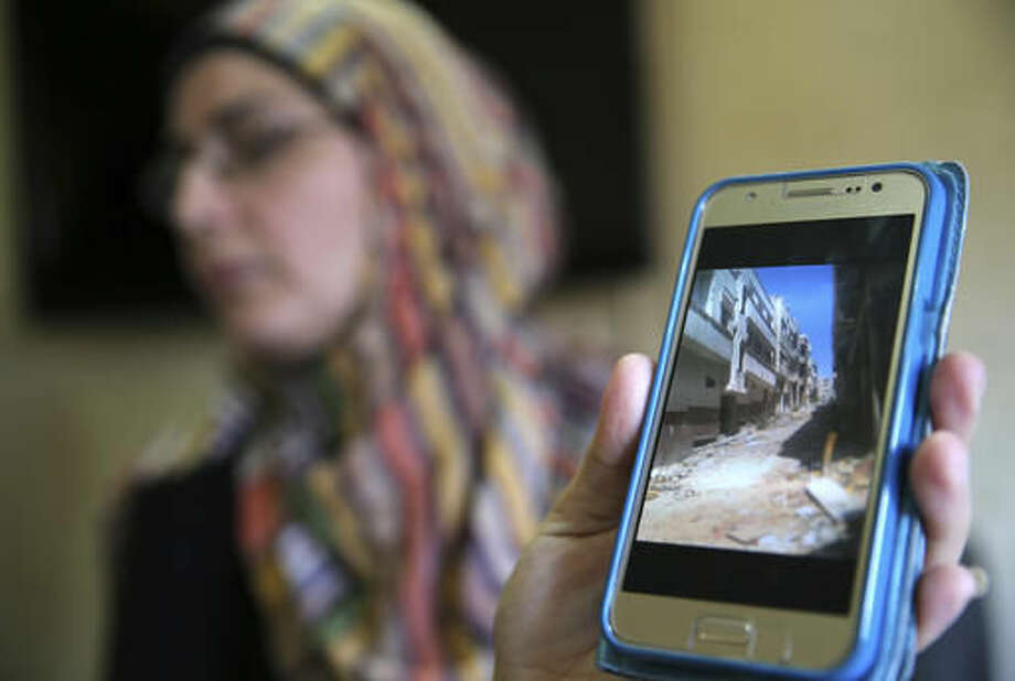 In this picture taken on Friday, Oct. 3, 2016, Hoda a Syrian displaced woman shows through her mobile phone the empty street of her house at Baba Tadmor neighborhood in Homs province, as she speaks during an interview with the Associated Press, in Tripoli, north Lebanon. Syrian opposition figures and refugees point to an array of obstacles facing the displaced who want to return home, saying that the government is machinating to discourage potentially restive populations from returning to areas they fled during the war. (AP Photo/Hussein Malla)