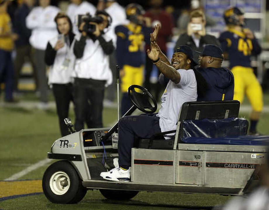 Retired NFL running back Marshawn Lynch waves to fans as he drives an injury cart onto the field with rapper E-40 prior to an NCAA college football game between Washington and California on Saturday, Nov. 5, 2016, in Berkeley, Calif. (AP Photo/Ben Margot)