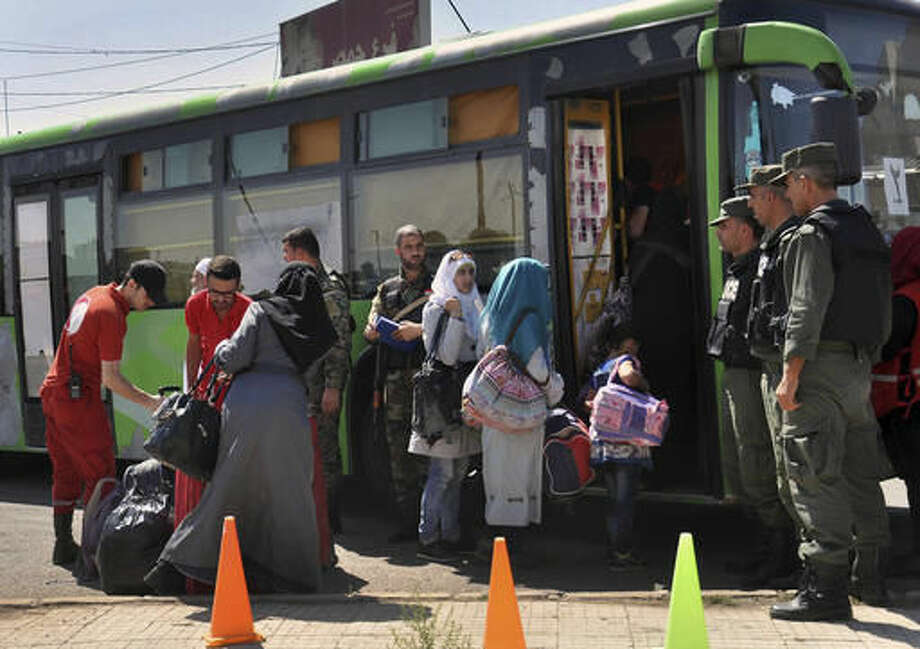 FILE - In this Monday, Sept. 26, 2016, file photo, released by the Syrian official news agency SANA, families of anti-Syrian government fighters, head to a bus as they leave the last besieged rebel-held neighborhood of Al-Waer in Homs province, Syria. Syrian opposition figures and refugees point to an array of obstacles facing the displaced who want to return home, saying that the government is machinating to discourage potentially restive populations from returning to areas they fled during the war. (SANA via AP, File)