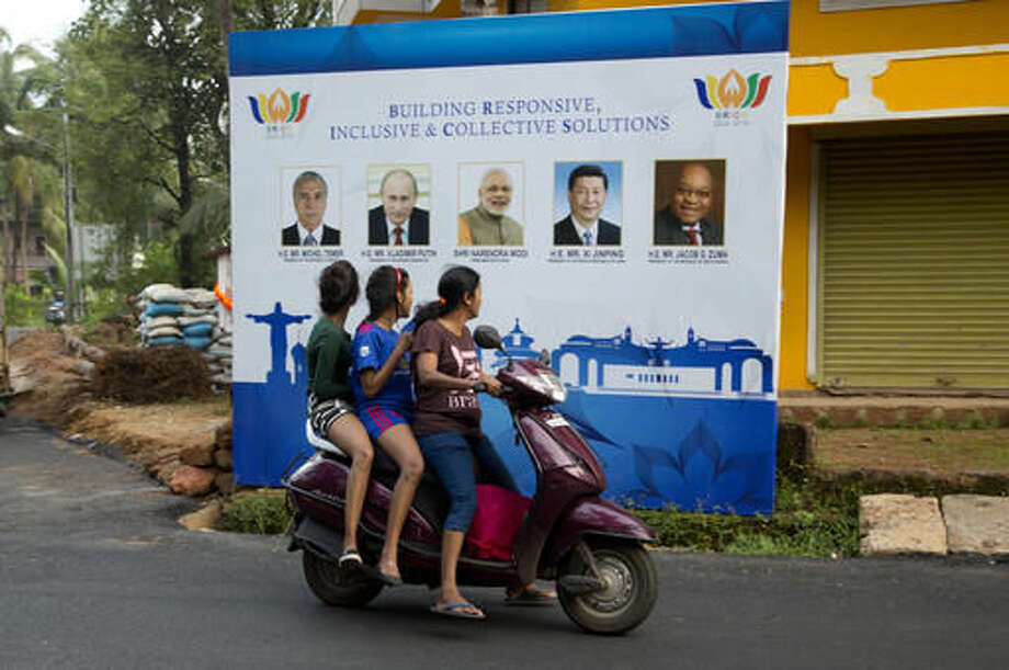 Indian girls on a scooter watch the poster of BRICS with the photographs of their leaders, in Goa, Thursday, Oct. 13, 2016. India will host the 8th Brazil, Russia, India, China and South Africa or BRICS Summit during its Chairmanship, which is scheduled to take place on 15-16 October 2016 in Indian western state of Goa. (AP Photo/Anupam Nath)