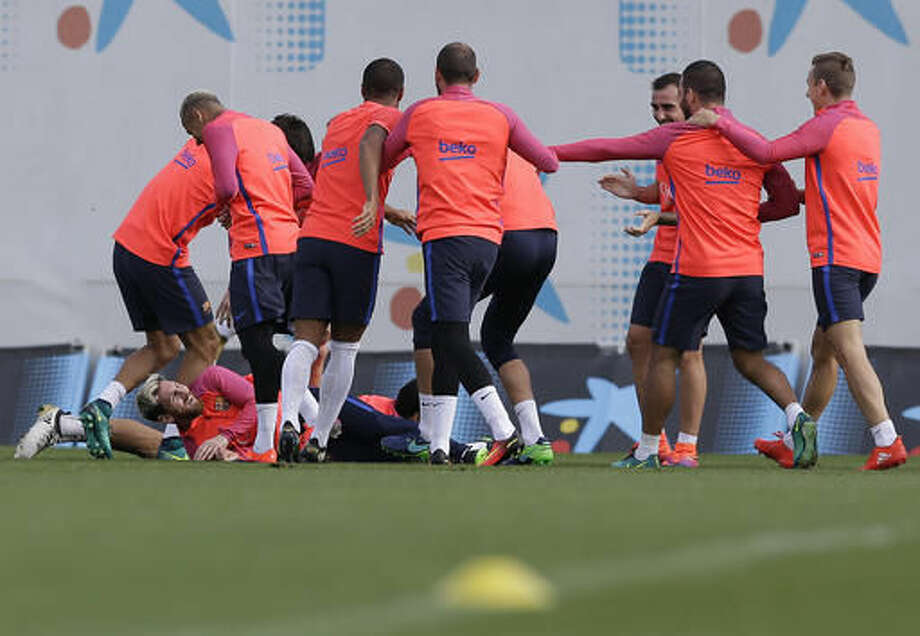 FC Barcelona's Lionel Messi, left on ground, reacts with his teammates during a training session at the Sports Center FC Barcelona Joan Gamper in Sant Joan Despi, Spain, Friday, Oct. 14, 2016. (AP Photo/Manu Fernandez)