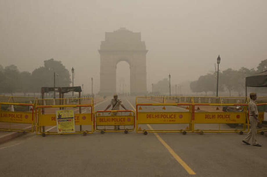 A Delhi policeman stands guard at the war memorial India Gate engulfed in a thick smog in New Delhi, India, Sunday, Nov. 6, 2016. The Delhi government has ordered that all city schools be shut, construction activity halted and all roads be doused with water as crippling air pollution has engulfed the Indian capital. The city, one of the world's dirtiest, has seen the levels of PM2.5 soar to over 900 microgram per cubic meter on Saturday, more than 90 times the level considered safe by the World Health Organization and 15 times the Indian government's norms. (AP Photo/Manish Swarup)