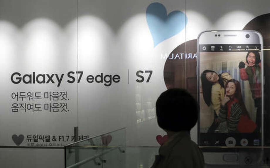 A woman walks by an advertisement of the Samsung Electronics Galaxy S7 Edge and S7 smartphone in Seoul, South Korea, Friday, Oct. 14, 2016. Samsung Electronics said Friday that the discontinuation of the Galaxy Note 7 would cost the company about $3 billion during the current and next quarters, bringing the total cost of the recall to at least $5.3 billion. The company said it will expand sales of two other smartphones released in spring, the Galaxy S7 and Galaxy S7 Edge, quashing rumors that it may try to release updated versions of those devices. (AP Photo/Lee Jin-man)