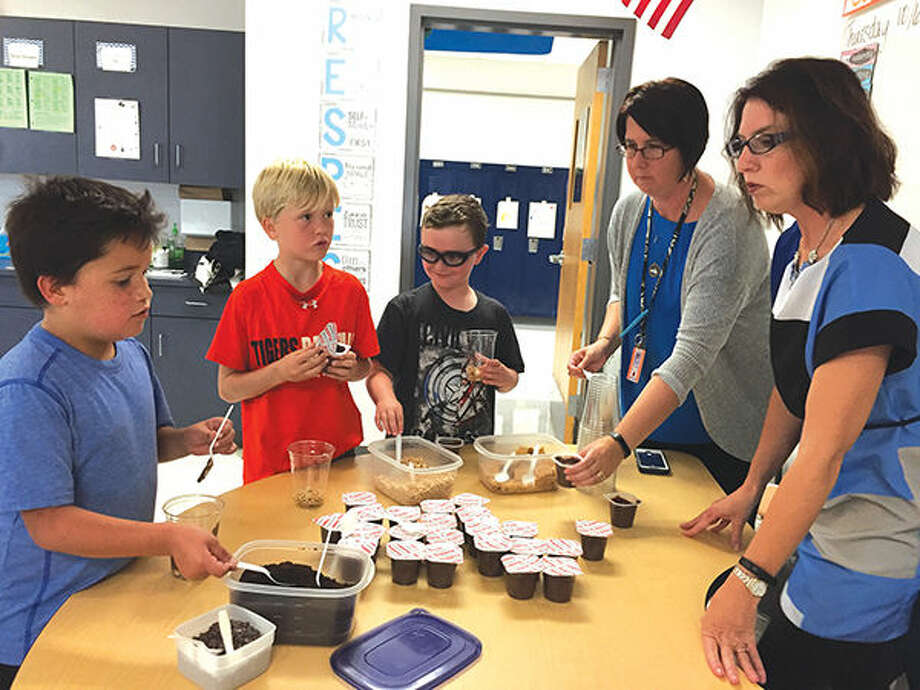 Cassens fourth graders, from left, Donovan Kagy,Gavin Ipanis and Gavin Lankford mix their edible soil samples under the eyes of Natalie Thiems, fourth/fifth-grade special education teacher, and fourth-grade classroom teacher Gina Law.