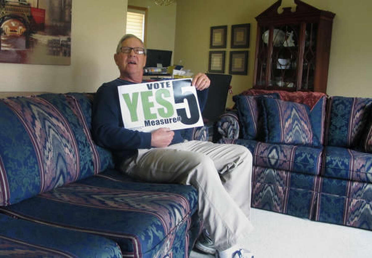 FILE - In this Oct. 21, 2016 file photo financial adviser Rilie Ray Morgan holds a sign promoting an initiated measure that would legalize the use of medical marijuana while sitting in his south Fargo, N.D. home. Morgan, who suffers from chronic pain, says he has never used marijuana as a pain reliever but would like the option of doing so. The group sponsoring the measure began a series of last-minute TV and online ads ahead of the Nov. 8 election. (AP Photo/Dave Kolpack, File)
