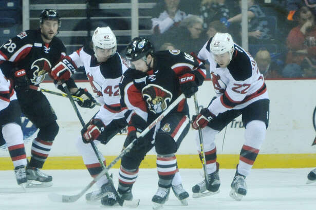 Kevin Rooney, left, and Ryan Kujawinski, right, of the Albany Devils fight for control of the puck against Jason Akeson of the Binghamton Senators during their game on Sunday, April 3, 2016, in Albany, N.Y.   (Paul Buckowski / Times Union) ORG XMIT: MER2016120116444378