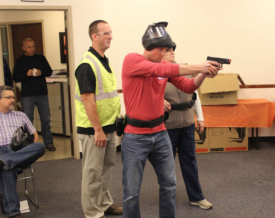 Adam Davis, 28, of Edwardsville, practices using an airsoft pistol at Thursday night's police academy session. Instructed by Sgt. Matt Breihan, participants were able to evaluate the use of force with pistols and OC spray, equipped in a duty belt while undergoing various police scenarios.