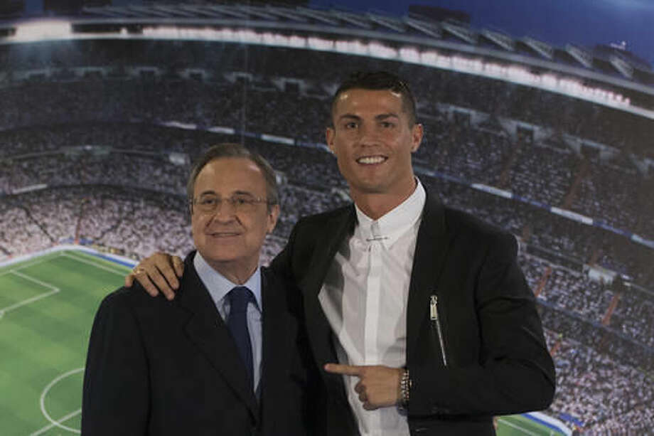 Real Madrid's Cristiano Ronaldo, right, poses with the club's President Florentino Perez after signing a new contract at the Santiago Bernabeu stadium in Madrid, Spain, Monday, Nov. 7, 2016. Real Madrid have extend Ronaldo's contract until June 2021, when the three-time world player of the year will be 36. Financial details were not released, although the star forward is expected to remain the team's top-paid player. (AP Photo/Paul White)