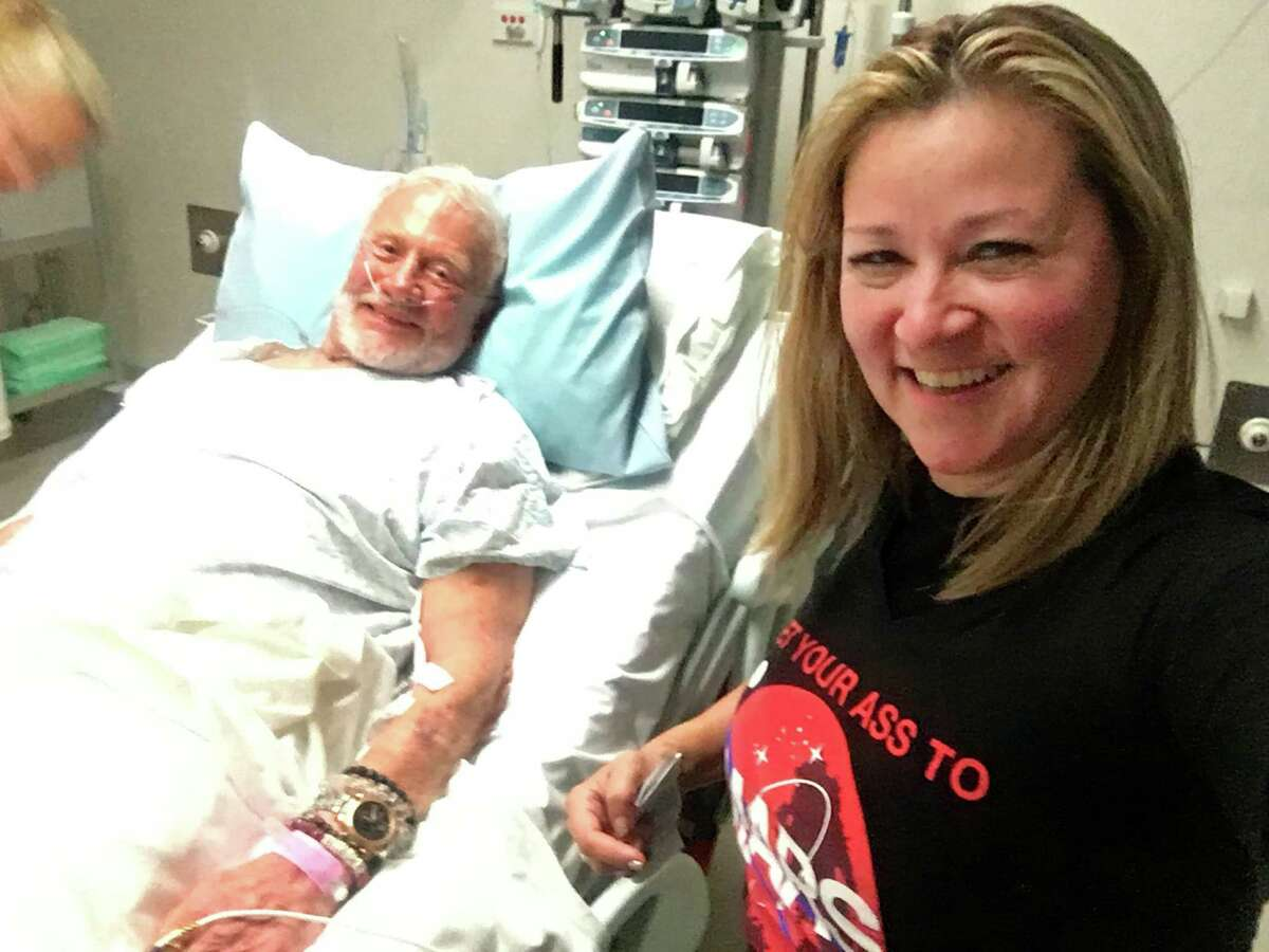 In this Thursday, Dec. 1, 2016 photo provided by Christina Korp, right, Buzz Aldrin lies in a hospital bed in Christchurch, New Zealand. Aldrin, the second man to walk on the moon, was evacuated from the South Pole to New Zealand where he was hospitalized in stable condition. (Christina Korp via AP) ORG XMIT: NY119
