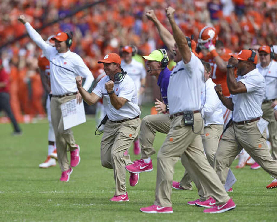 Clemson head coach Dabo Swinney, center, along with staff members, reacts during the second half of an NCAA college football game against North Carolina State Saturday, Oct. 15, 2016, in Clemson, S.C. Clemson won 24-17 in overtime. (AP Photo/Richard Shiro)