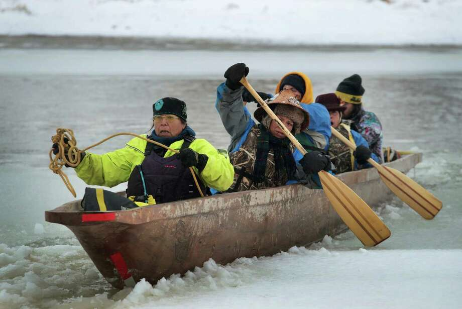 CANNON BALL, ND - DECEMBER 01:  Native Americans from Washington state arrive at Oceti Sakowin Camp on the edge of the Standing Rock Sioux Reservation after traveling from the headwaters of the Missouri River in a dugout canoe on December 1, 2016 outside Cannon Ball, North Dakota. Native Americans and activists from around the country have been gathering at the camp for several months trying to halt the construction of the Dakota Access Pipeline. The proposed 1,172-mile-long pipeline would transport oil from the North Dakota Bakken region through South Dakota, Iowa and into Illinois.  (Photo by Scott Olson/Getty Images) ORG XMIT: 685290013 Photo: Scott Olson / 2016 Getty Images