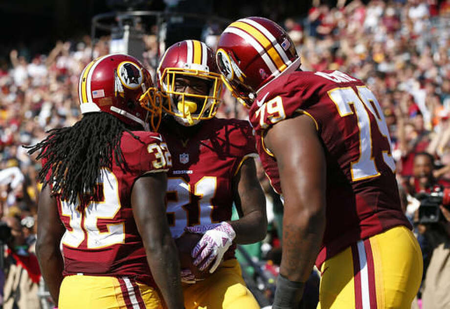 Washington Redskins running back Matt Jones, center, celebrates his touchdown with teammates Rob Kelley, left, and Ty Nsekhe in the first half of an NFL football game against the Philadelphia Eagles, Sunday, Oct. 16, 2016, in Landover, Md. (AP Photo/Alex Brandon)