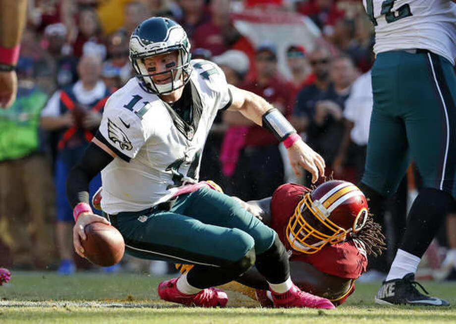 Philadelphia Eagles quarterback Carson Wentz, left, is sacked by Washington Redskins defensive end Ricky Jean Francois in the second half of an NFL football game, Sunday, Oct. 16, 2016, in Landover, Md. Washington won 27-20. (AP Photo/Alex Brandon)