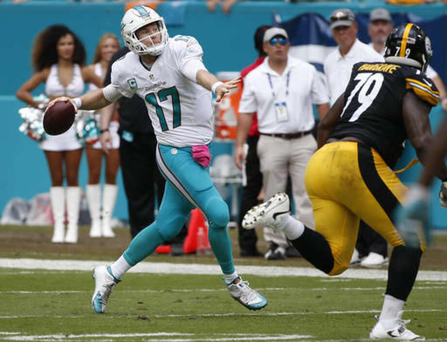 Miami Dolphins quarterback Ryan Tannehill (17) runs and looks to pass, during the first half of an NFL football game against the Pittsburgh Steelers, Sunday, Oct. 16, 2016, in Miami Gardens, Fla. To the right is Pittsburgh Steelers nose tackle Javon Hargrave (79). (AP Photo/Wilfredo Lee)