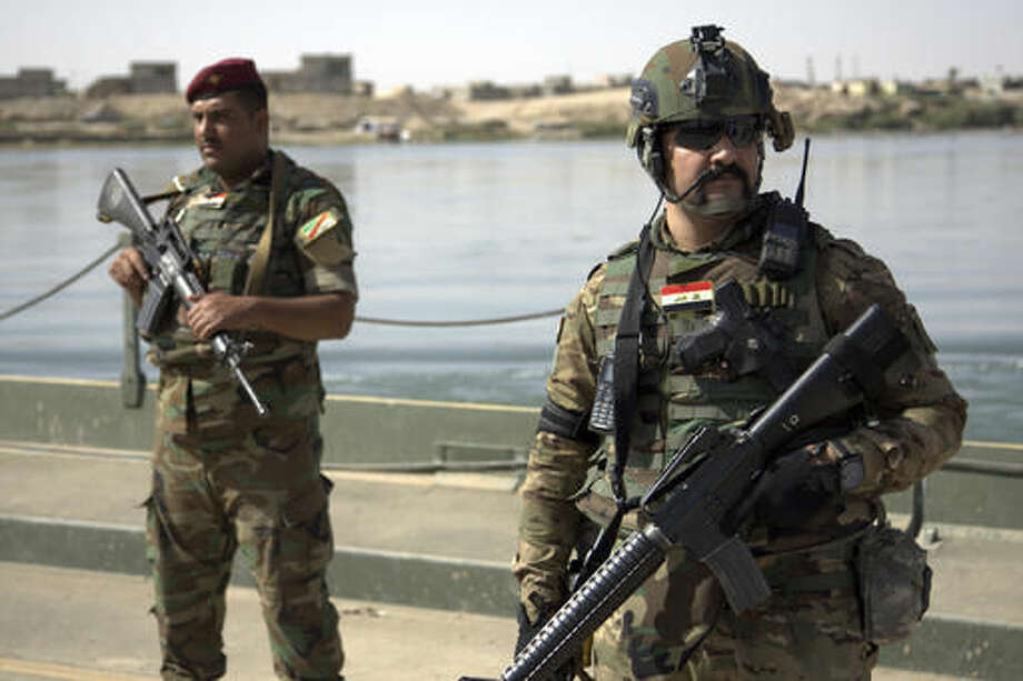 FILE -- In this Saturday, Oct. 15, 2016 file photo, Iraqi soldiers secure a temporary pontoon bridge near Qayara Air Base, northern Iraq. Iraqi forces appear poised to launch their most complex anti-IS operation to date: retaking the country's second largest city of Mosul. While the country's military has won a string of territorial victories that have pushed IS out of more than half of the territory the group once held, some Iraqi officials worry that the Mosul fight has been rushed and if the city is retaken without a plan to broker a peace, it could lead to more violence. (AP Photo/Adam Schreck, File)