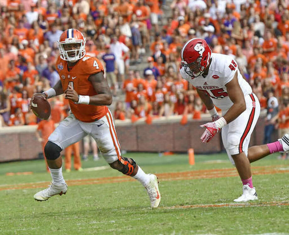 Clemson quarterback Deshaun Watson, left, scrambles out of the pocket while pursued by North Carolina State's Darian Roseboro during the second half of an NCAA college football game Saturday, Oct. 15, 2016, in Clemson, S.C. Clemson won 24-17 in overtime. (AP Photo/Richard Shiro)