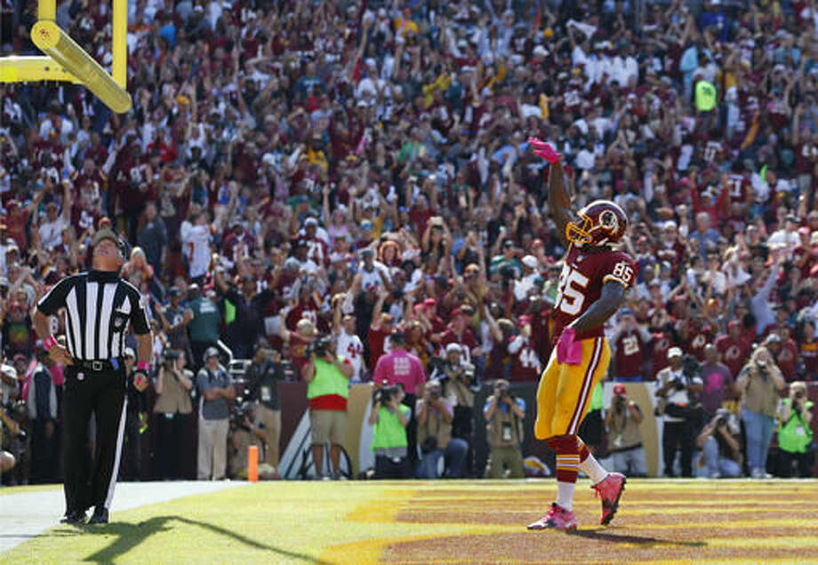 "FILE - In this Oct. 16, 2016, file photo, Washington Redskins tight end Vernon Davis celebrates after scoring a touchdown in the first half of an NFL football game against the Philadelphia Eagles in Landover, Md. Using the ball ""as a prop"" is illegal. The 15-yard penalty assessed on the kickoff led to a shorter kick that was returned 86 yards for a score by Philadelphia's Wendell Smallwood. (AP Photo/Alex Brandon, File)"