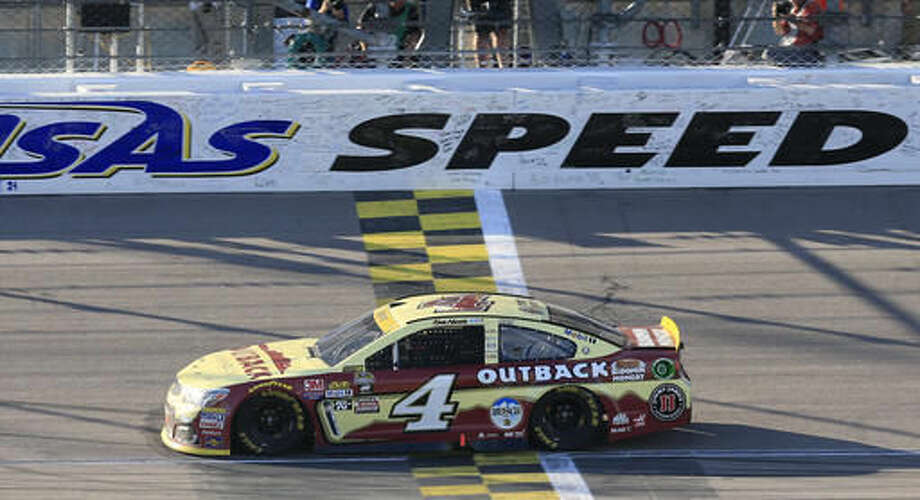 NASCAR driver Kevin Harvick (4) crosses the finish line to a Sprint Cup series auto race at Kansas Speedway in Kansas City, Kan., Sunday, Oct. 16, 2016. (AP Photo/Orlin Wagner)