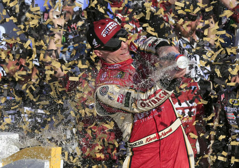 NASCAR driver Kevin Harvick celebrates in victory lane after winning a Sprint Cup series auto race at Kansas Speedway in Kansas City, Kan., Sunday, Oct. 16, 2016. (AP Photo/Orlin Wagner)