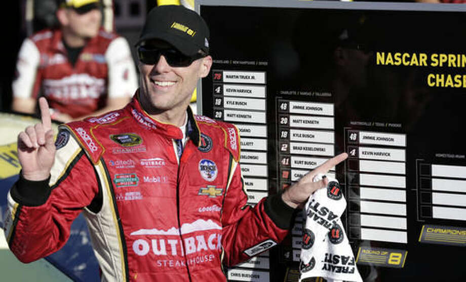 Kevin Harvick points to his advancement in the chase after winning a Sprint Cup Series auto race at Kansas Speedway in Kansas City, Kan., Sunday, Oct. 16, 2016. (AP Photo/Colin E. Braley)