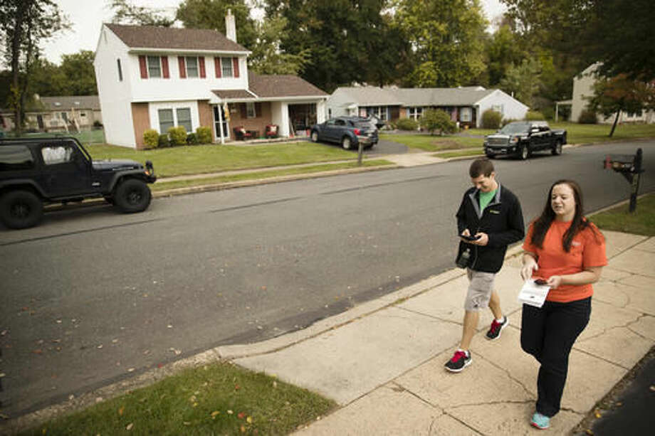 In this photo taken Oct. 13, 2016, Kathryn Ferro and Stephen McGee with Americans for Prosperity walk to knock on a voter's door in Bensalem, Pa. The Republican door-knockers are busy selling Pennsylvania Sen. Pat Toomey, and they never mention Donald Trump. Such is the 2016 landscape in battleground across the country, where hundreds of activists tied to the billionaire Koch brothers are eschewing the top of the ticket in favor of protecting the Republican majority in the Senate. (AP Photo/Matt Rourke)