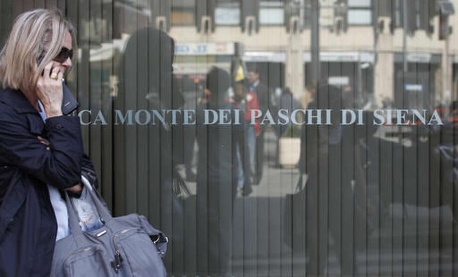 FILE - In this Wednesday, May 9, 2012 file photo, a woman walks past a Monte Dei Paschi di Siena bank branch in Milan, Italy. Zombies are gnawing at Europe's underpowered economic recovery _ zombie banks and zombie companies. Almost a decade after the financial crisis that ravaged the global economy, economists and top officials are warning that troubles in the banking system are keeping growth slow and unemployment high. (AP Photo/Luca Bruno, File)