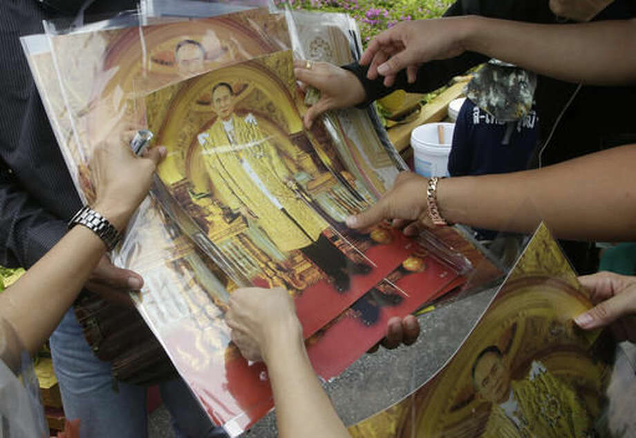 Mourners buy portraits of the late Thai King Bhumibol Adulyadej outside the Grand Palace in Bangkok, Thailand, Monday, Oct. 17, 2016. Tens of thousands of people are thronging at the palace complex to pay their last respects to a beloved monarch who dominated the memories of generations of Thais. (AP Photo/Sakchai Lalit)