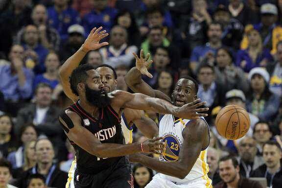 James Harden (13) is guarded by Draymond Green (23) and Andre Iguodala (9) during the first half as the Golden State Warriors played the Houston Rockets at Oracle Arena in Oakland, Calif., on Thursday, December 1, 2016.