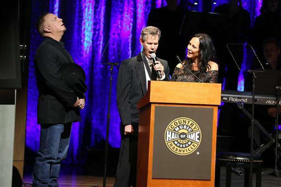 "From left, artist Garth Brooks, artist Randy Travis and Mary Travis sing ""Amazing Grace"" at the Country Music Hall of Fame Medallion Ceremony at the Country Music Hall of Fame and Museum on Sunday, Oct. 16, 2016 in Nashville, Tenn. (Photo by Laura Roberts/Invision/AP)"