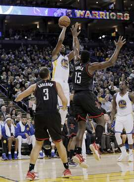 Kevin Durant (35) puts in a shot defended by Montrezl Harrell (5) during the first half as the Golden State Warriors played the Houston Rockets at Oracle Arena in Oakland, Calif., on Thursday, December 1, 2016.