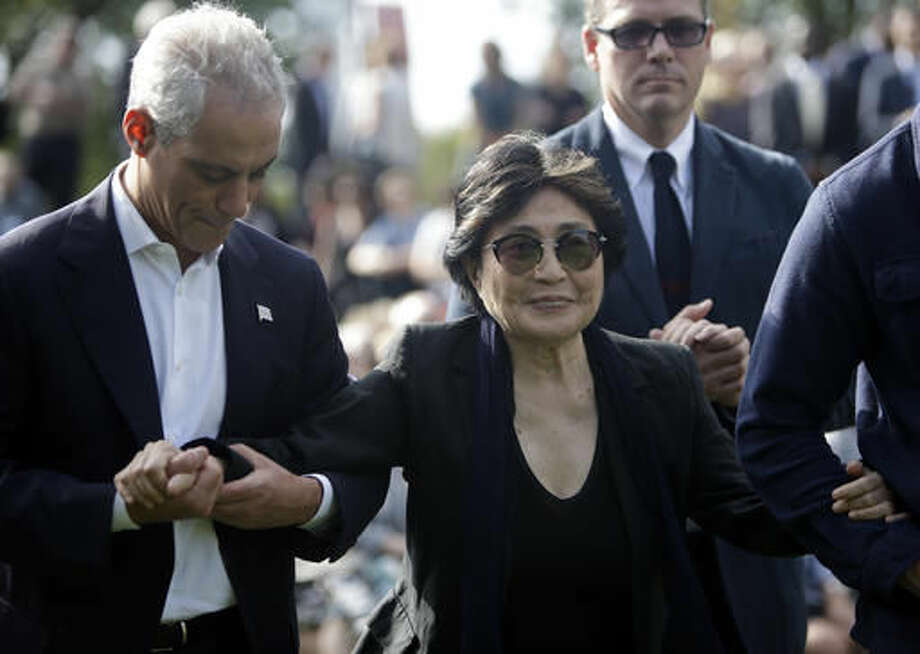 Chicago Mayor Rahm Emanuel, left, assists Yoko Ono after the dedication ceremony for the permanent art installation of a sculpture, SKYLANDING, Monday, Oct. 17, 2016, in Chicago. SKYLANDING is Ono's first permanent public art installation in the United States. (AP Photo/Kiichiro Sato)
