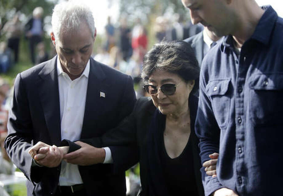Chicago Mayor Rahm Emanuel, left, helps Yoko Ono after the dedication ceremony for the permanent art installation of a sculpture, SKYLANDING, Monday, Oct. 17, 2016, in Chicago. SKYLANDING is Ono's first permanent public art installation in the United States. (AP Photo/Kiichiro Sato)
