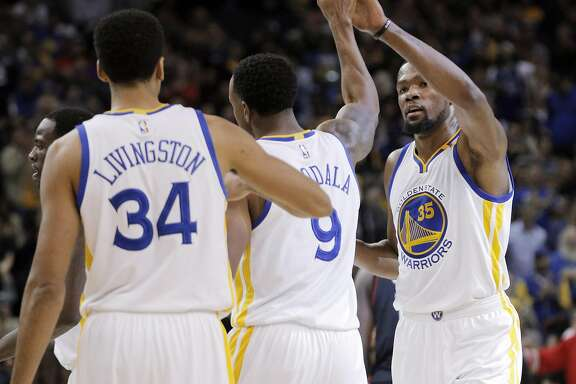 Kevin Durant (35) high fives Andre Iguodala (9) after a scoring play for the Warriors during the first half as the Golden State Warriors played the Houston Rockets at Oracle Arena in Oakland, Calif., on Thursday, December 1, 2016.