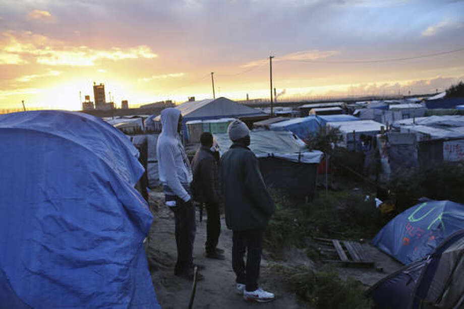 Migrants stand in a makeshift migrants camp near Calais, France, Sunday, Oct. 16, 2016. The government is gradually deporting migrants without right to asylum and relocating the rest to more than 160 centers around France. It is expected to close the camp in the coming weeks but no official dates have been announced. (AP Photo/Thibault Camus)