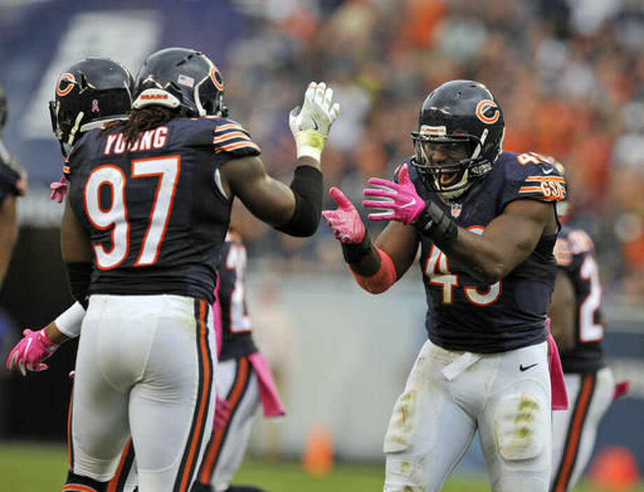 Chicago Bears running back Joique Bell (43) and outside linebacker Willie Young (97) celebrate a fumble recovery against the Jacksonville Jaguars during the second half of an NFL football game in Chicago, Sunday, Oct. 16, 2016. (AP Photo/Paul Beaty)