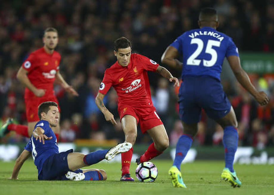 Liverpool's Philippe Coutinho, centre, vies for the ball with Manchester United's Ander Herrera, left, during the English Premier League soccer match between Liverpool and Manchester United at Anfield stadium in Liverpool, England, Monday, Oct. 17, 2016. (AP Photo/Dave Thompson)