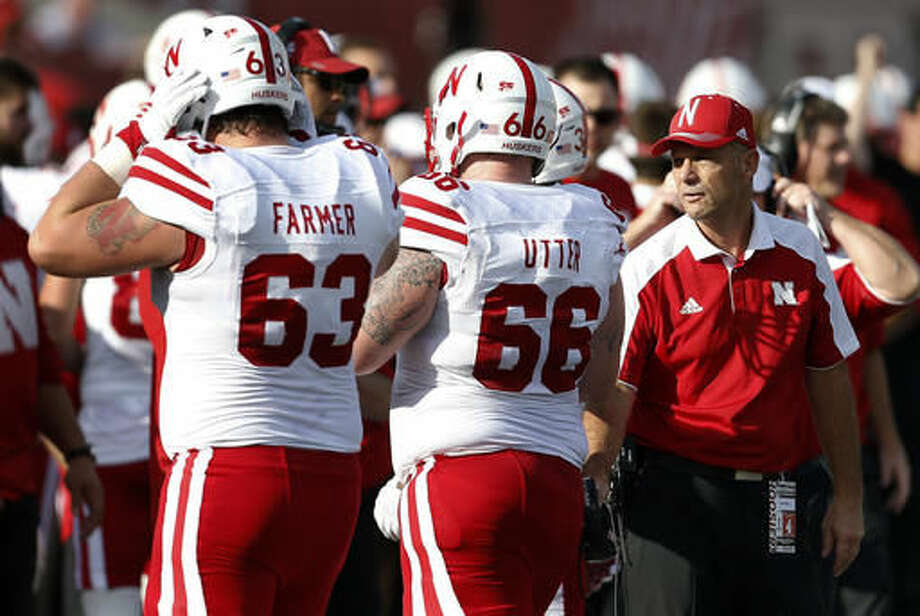 Nebraska head coach Mike Riley chats with Nebraska offensive lineman Dylan Utter (66) after a play against Indiana in the first half of an NCAA college football game in Bloomington, Ind., Saturday, Oct. 15, 2016. Nebraska won the game 27-22. At far left is Nebraska offensive lineman Tanner Farmer (63). (AP Photo/Sam Riche)