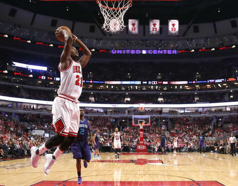 Chicago Bulls' Jimmy Butler goes up for a dunk past Charlotte Hornets' Marvin Williams during the first half of an NBA preseason basketball game Monday, Oct. 17, 2016, in Chicago. (AP Photo/Charles Rex Arbogast)