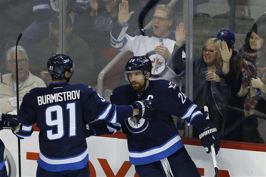 Winnipeg Jets' Alexander Burmistrov (91) and Blake Wheeler (26) celebrate Wheeler's goal against the Boston Bruins during first period NHL hockey action in Winnipeg, Manitoba, Monday, Oct. 17, 2016. (John Woods/The Canadian Press via AP)