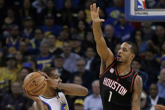 Golden State Warriors' Kevin Durant, left, looks to pass away from Houston Rockets' Trevor Ariza (1) during the first half of an NBA basketball game Thursday, Dec. 1, 2016, in Oakland, Calif. (AP Photo/Ben Margot)