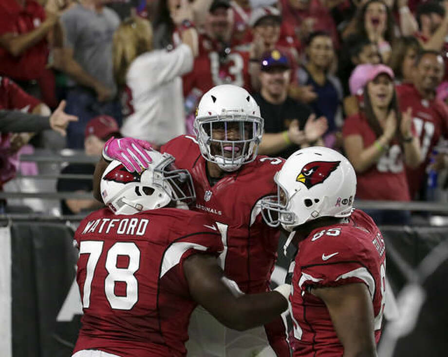 Arizona Cardinals running back David Johnson, center, celebrates his touchdown run with guard Earl Watford (78) and tight end Darren Fells (85) during the first half of an NFL football game against the New York Jets, Monday, Oct. 17, 2016, in Glendale, Ariz. (AP Photo/Rick Scuteri)