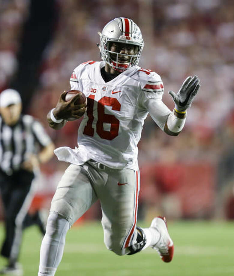 FILE - In this Oct. 15, 2016, file photo, Ohio State quarterback J.T. Barrett (16) scrambles against Wisconsin during the first half of an NCAA college football game, in Madison, Wis. Barrett was big-time in prime time last week and now he has two more showcase games in the next three weeks to boost his Heisman Trophy hopes. (AP Photo/Andy Manis, File)