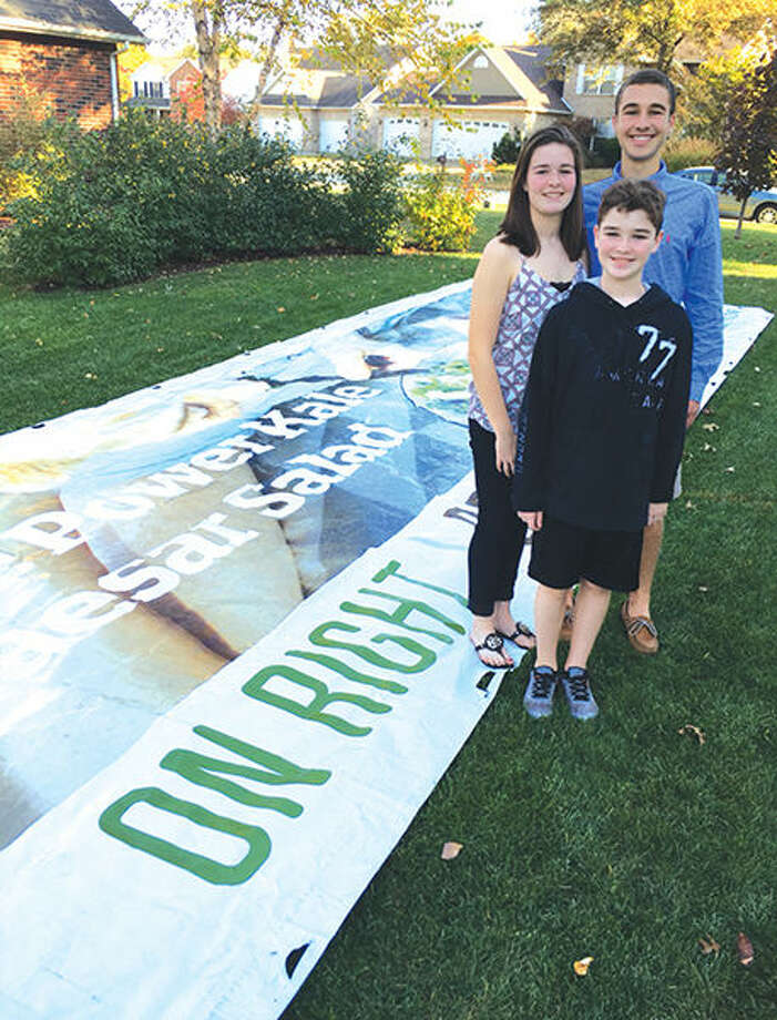 August Windau, in back, with siblings Regan Windau and George Windau with one of the vinyl billboards they have collected.