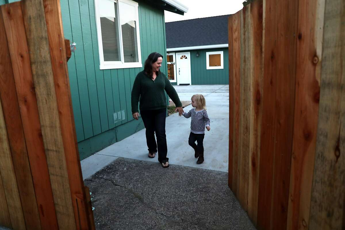 On their way to check the mail, Toni Gardner and her granddaughter Amelia, 2, leave the small house that she had built in the backyard of her residence in Santa Cruz, Calif., on Thursday, December 1, 2016.